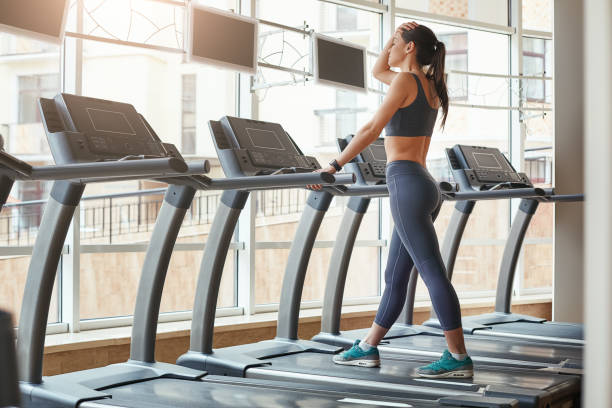 i can not run anymore. full length of young women in sports clothing keeping hand on forehead and feeling tired while running on a treadmill at gym. - runner rehab gym foto e immagini stock