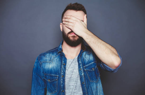 I can not see anything. A young man in a denim shirt closes his eyes with his hand against a gray background. I can not see anything. A young man in a denim shirt closes his eyes with his hand against a gray background. head in hands stock pictures, royalty-free photos & images