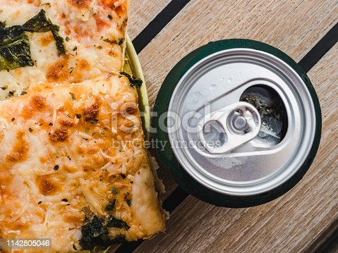 183064447 istock photo Can of beer and a piece of pizza. Top view 1142805046