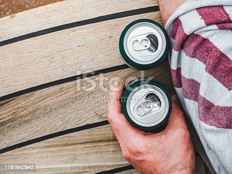 183064447 istock photo Can of beer and male hand. Top view 1191642942