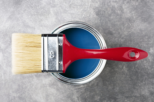 Can of paint with brush.