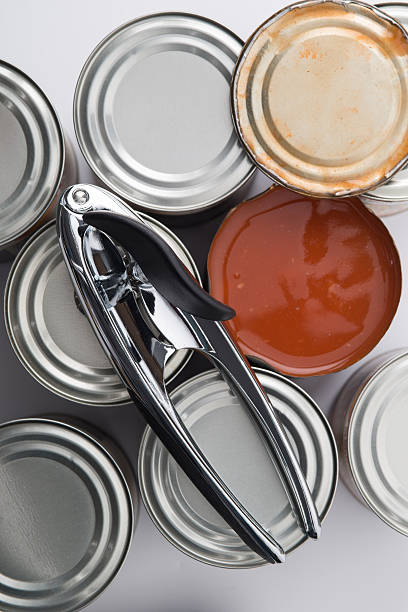 Can Opener on Tin Cans Beside Opened Can - foto de stock