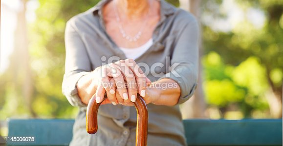 Cropped shot of an unrecognizable senior woman with her hands on her walking stick outdoors