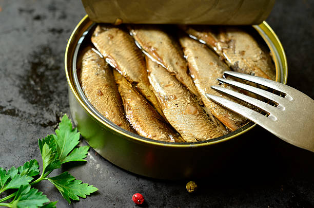 can with smoked baltic sprats. - herring stock photos and pictures