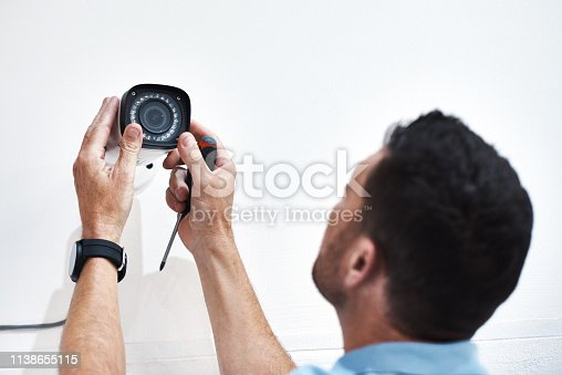 Shot of a mature man installing a security camera on a building