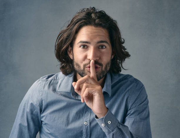 Can you keep a secret? Studio shot of a man posing with his finger on his lips against a grey background finger on lips stock pictures, royalty-free photos & images