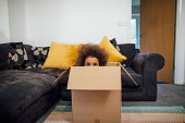 Mixed race girl popping her head out of a cardboard box in the sitting room at home.