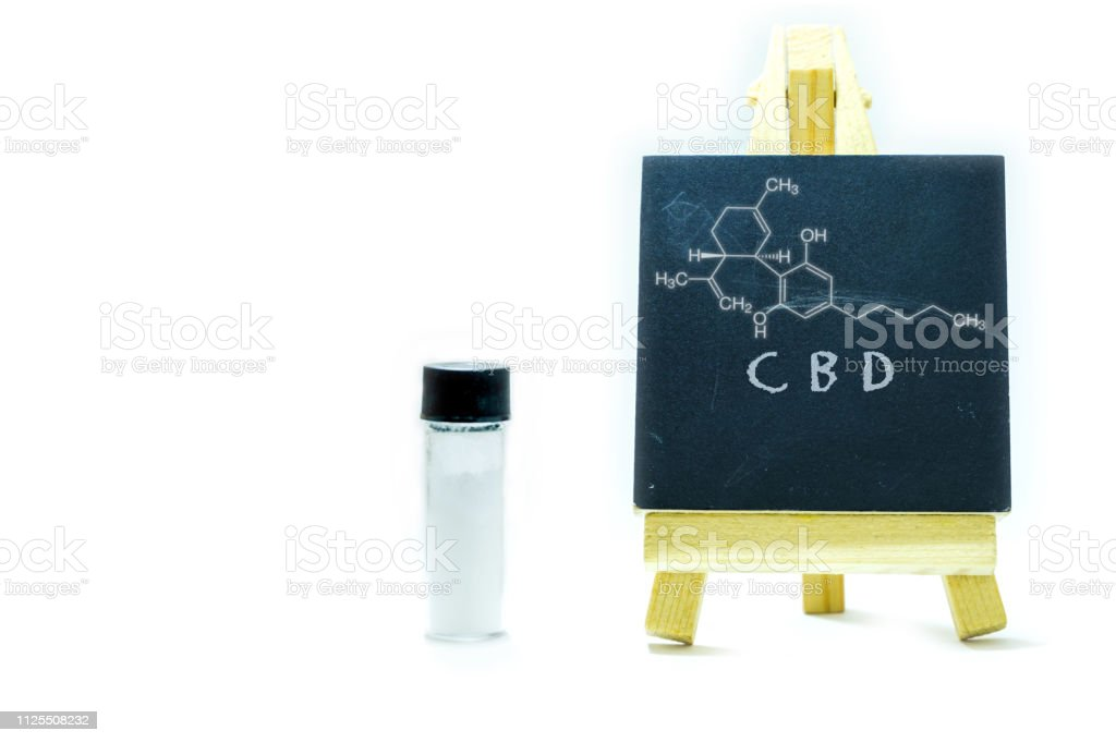 CBD Canabidiol crystals isolate in glass container with CBD chemical formula on chalk board stock photo