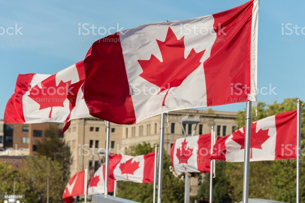 Canada and British Columbia flags waving over blue sky in Vancouver, BC, Canada stock photo