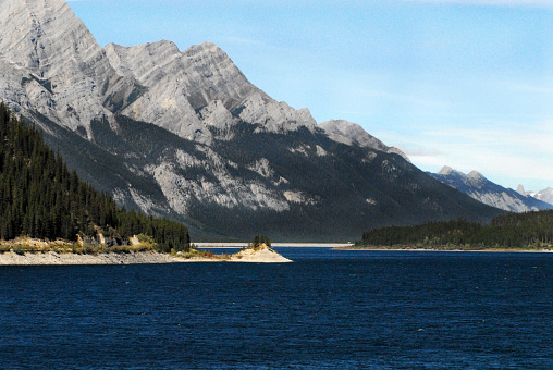 A beautiful panoramic landscape of a deep blue lake contrasting with green forests and the Rocky Mountains in the background.  Shot in the Banff, Canada National Park.