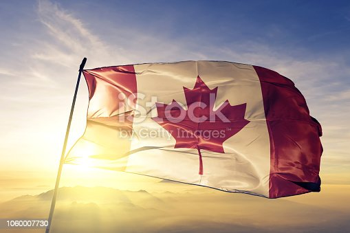 Canada Canadian flag on flagpole textile cloth fabric waving on the top sunrise mist fog