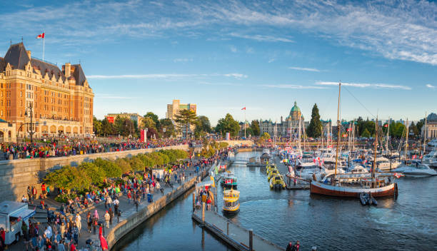 Canada Day in Victoria, Vancouver Island, Canada. Masses of people visiting the celebrations at inner harbour with the parliament building during sunset. stock photo