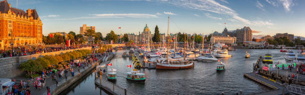 Canada Day in Victoria, Vancouver Island, Canada. Masses of people visiting the celebrations at inner harbour with the parliament building during sunset. Canada Day in Victoria, Vancouver Island, Canada. Masses of people visiting the celebrations at inner harbour with the parliament building during sunset. british columbia stock pictures, royalty-free photos & images