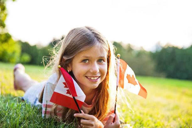 canada day - patriotic little girl with the canadian flag - canada day stock pictures, royalty-free photos & images