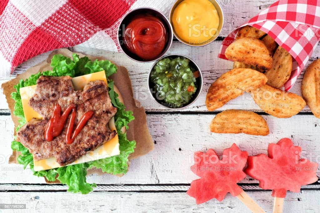 Canada Day picnic scene with maple leaf hamburger and watermelon stock photo