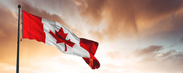 canada flag on sunset sky - canada day stock pictures, royalty-free photos & images