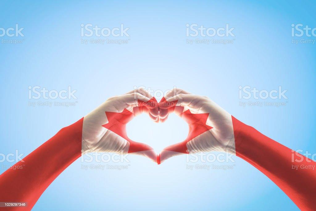 Canada flag pattern on people hands in heart shape for national...