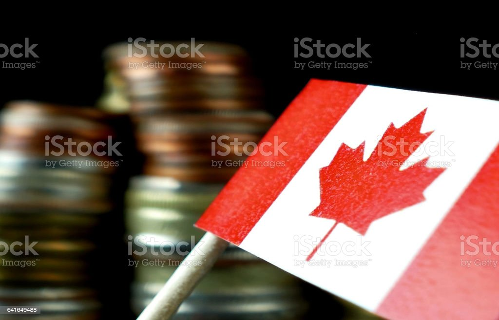 Canada flag waving with stack of money coins macro stock photo