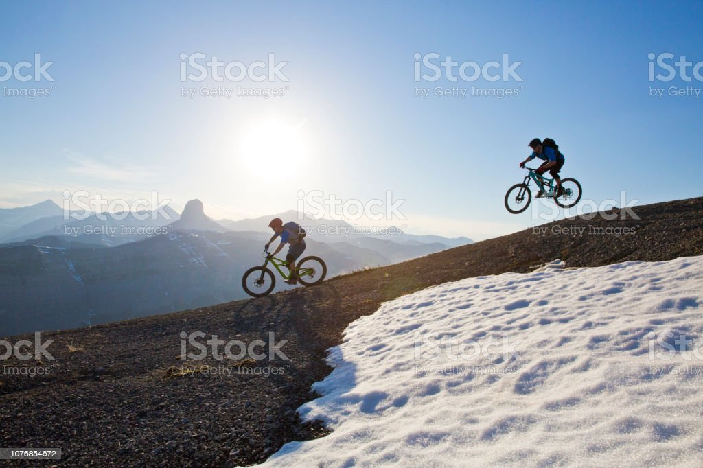 Two men enjoy a downhill mountain bike trail in the Rocky Mountains...