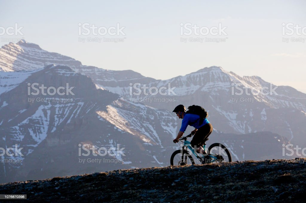 A male mountain bike rider goes down a trail in the Rocky Mountains...