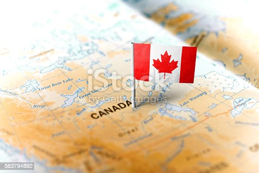 The flag of Canada pinned on the map. Horizontal orientation. Macro photography.