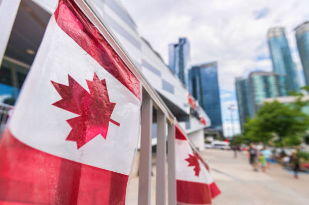 canada plastic flag with blurred urban background in toronto - canada stock photos and pictures