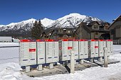 Canmore, Alberta, Canada - March 6, 2019: A Row of Canada Post Mailboxes with backdrop of Snowy Mountain Peaks in beautiful Canadian Rockies
