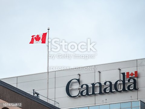 istock Canada Wordmark, the official logo of the Canadian government, on an administrative building next to a Canadian flag waiving 1074734812