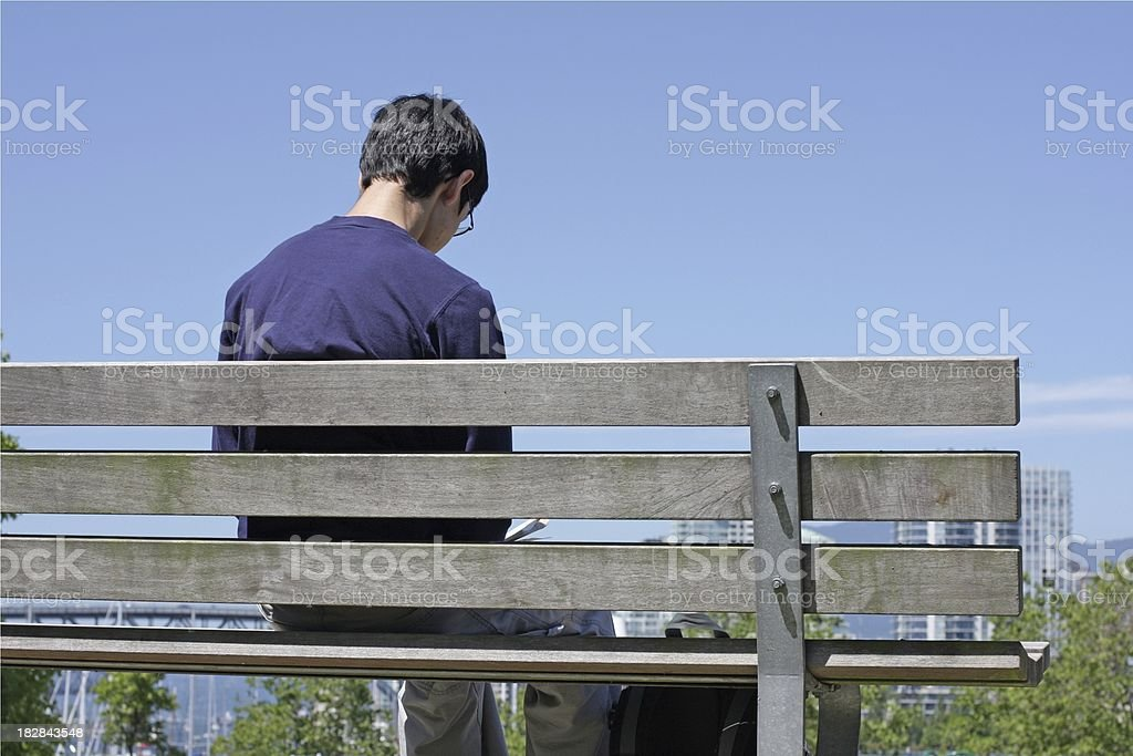 Canadaian Male Teen Sits Alone on a Park Bench, Vancouver royalty-free stock photo