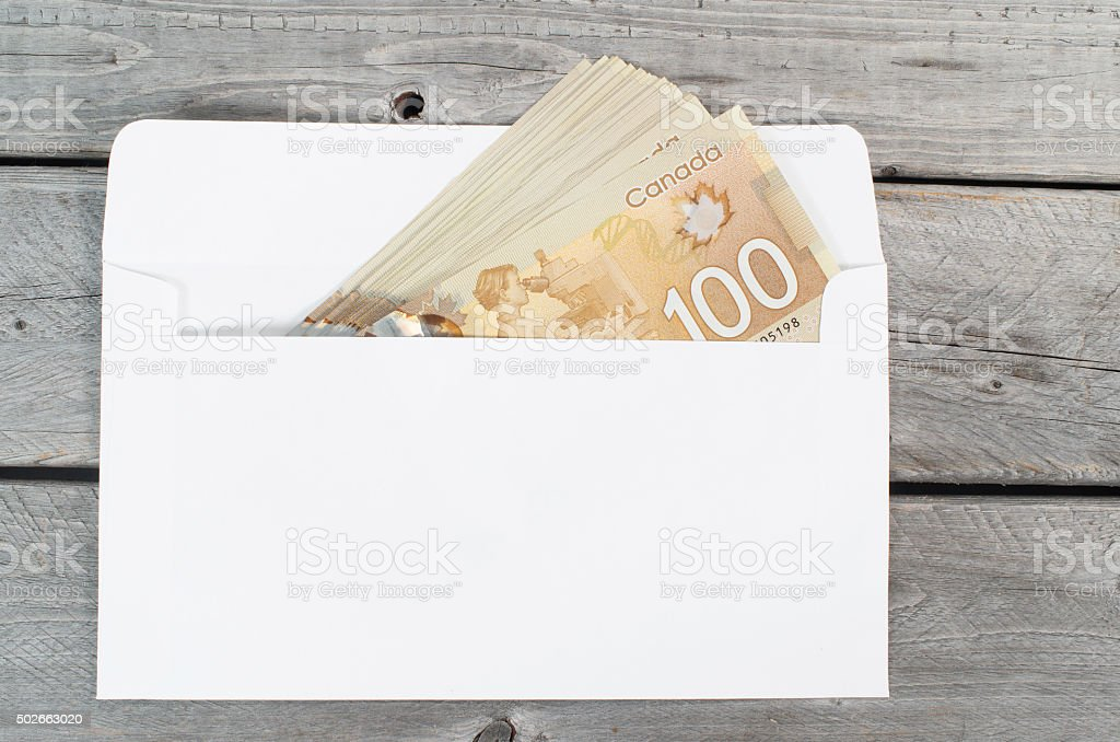 Canadian 100 bills in white envelope on a wooden table stock photo