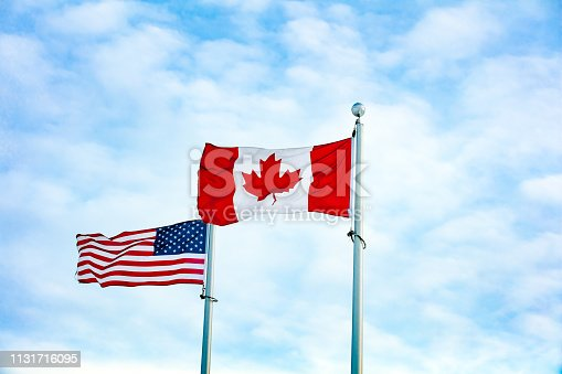 istock Canadian and American flag together 1131716095