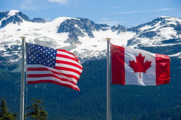 Canadian and American flags Canadian and American flags in the mountains canada flag photos stock pictures, royalty-free photos & images
