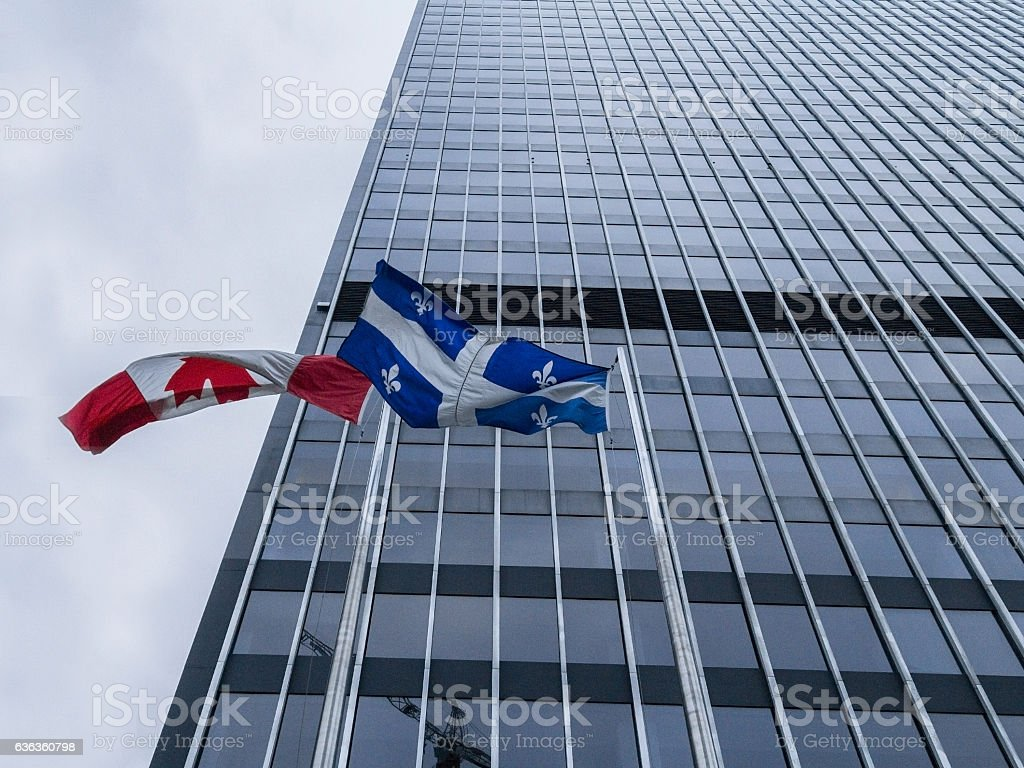 Canadian and Quebec flags in front of a skysrcaper stock photo