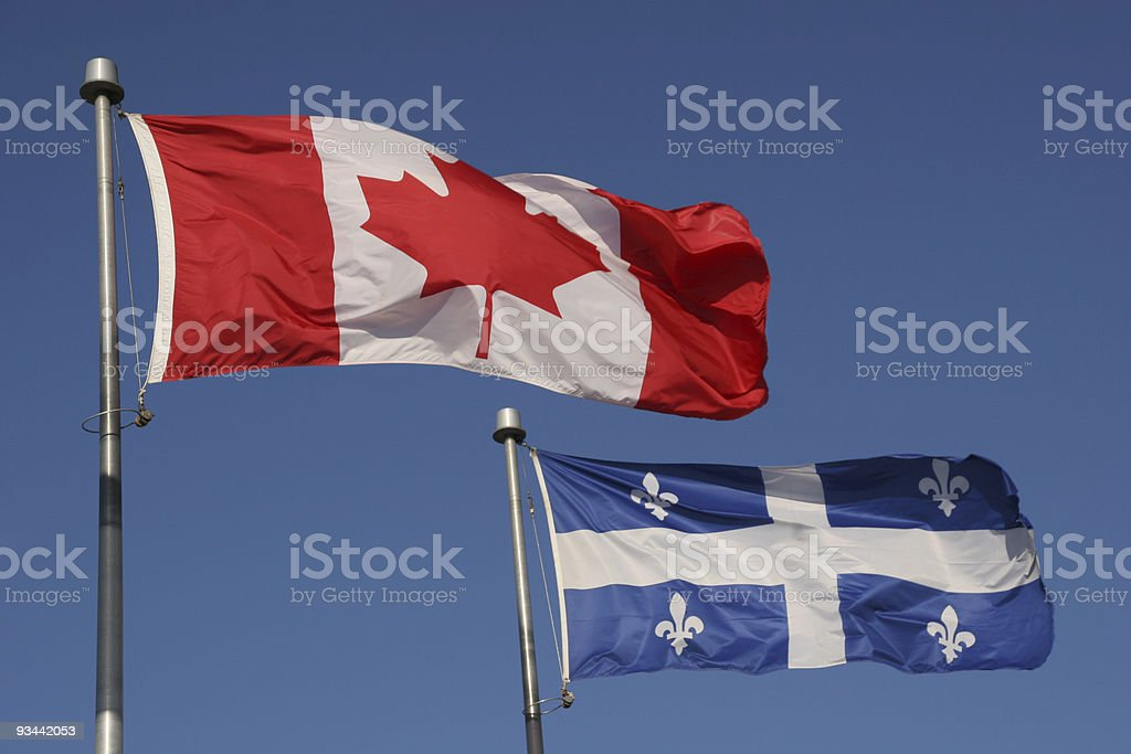 Canadian and Quebec provincial flags flying in a blue sky stock photo