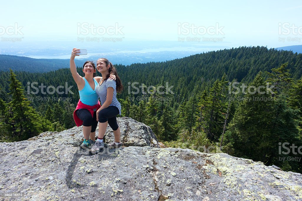 Canadian Asian Teenage Sisters Taking Cellphone Selfie on Mountain Top stock photo