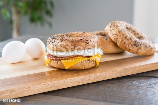 Canadian Bacon, egg and cheese breakfast sandwich with an everything bagel on cutting board