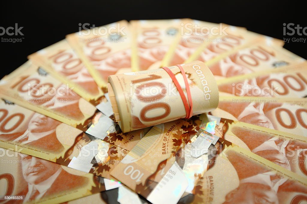 canadian fanned hundred dollar bills and roll of bills stock photo