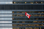 Canadian flag in front of a modern office building at dusk downtown Toronto, with illuminated office spaces.