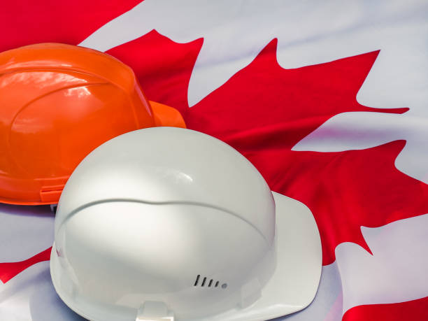drapeau canadien et deux casques protecteurs. plan rapproché - 1er mai photos et images de collection