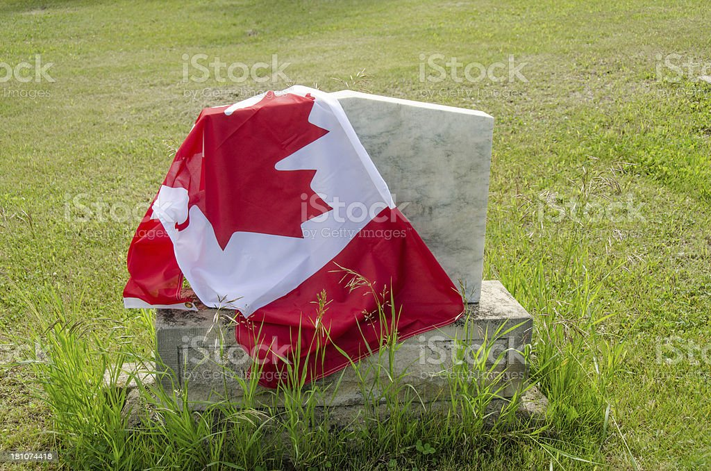 Canadian flag draped over a tombstone with green grass royalty-free stock photo