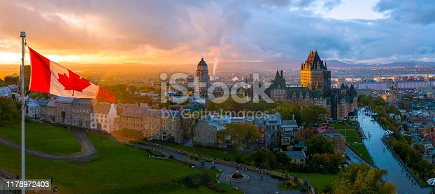 Aerial panorama view of Old Quebec City. To left side of frame is a Canadian flag in front of a beautiful golden sunset. To the right of the frame is Old Quebec, including the Chateau Frontenac and Defferin Terrace.