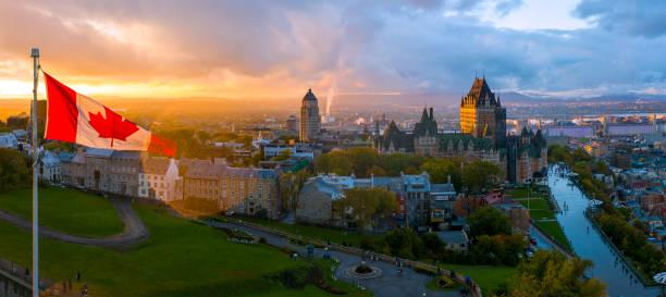kanadyjska flaga powiewająca nad malowniczym starym miastem quebec o zachodzie słońca - kanada zdjęcia i obrazy z banku zdjęć
