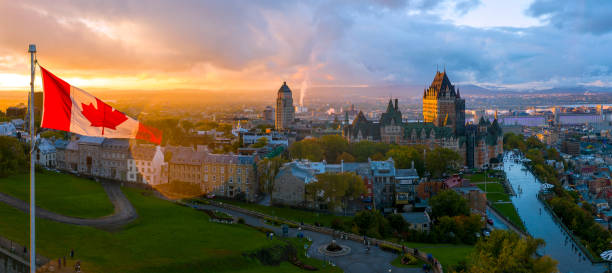 Canadian flag flying over a picturesque Old Quebec City at sunset Aerial panorama view of Old Quebec City. To left side of frame is a Canadian flag in front of a beautiful golden sunset. To the right of the frame is Old Quebec, including the Chateau Frontenac and Defferin Terrace. canada stock pictures, royalty-free photos & images