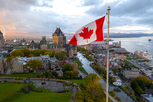A flowing Canadian flag on a flagpole. Taken at sunset with Old Quebec City and the St. Lawrence River in the background. Aerial HDR view.