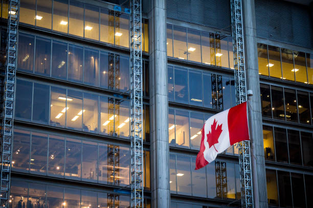 Canadian flag in front of a business building in Toronto, Ontario, Canada Picture of a flag of Canada waiving in the air in front of a business building in the city center of Toronto, the main city of Canada, and the economic and financial capital of the country. canada stock pictures, royalty-free photos & images