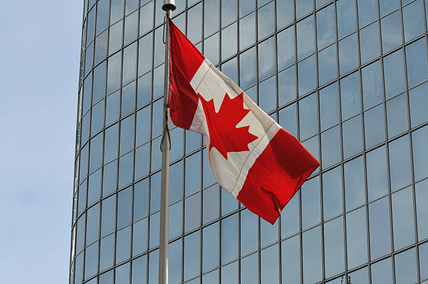 Canadian flag in front of skyscraper, Toronto stock photo