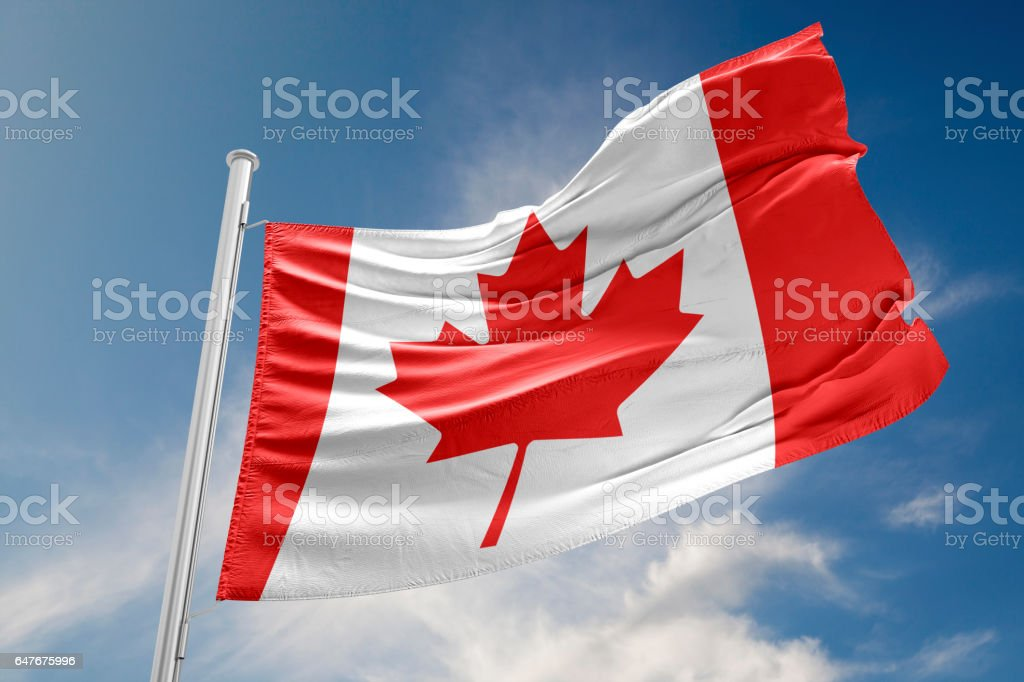 Canadian Flag is Waving Against Blue Sky stock photo