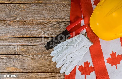 istock Canadian flag Labor Day two protective hardhats top view concept of labor and employment 1164818533