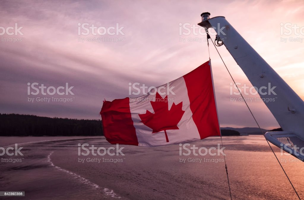 Canadian flag of a ferry ship at sunset at sea,Vancouver,Canada stock photo