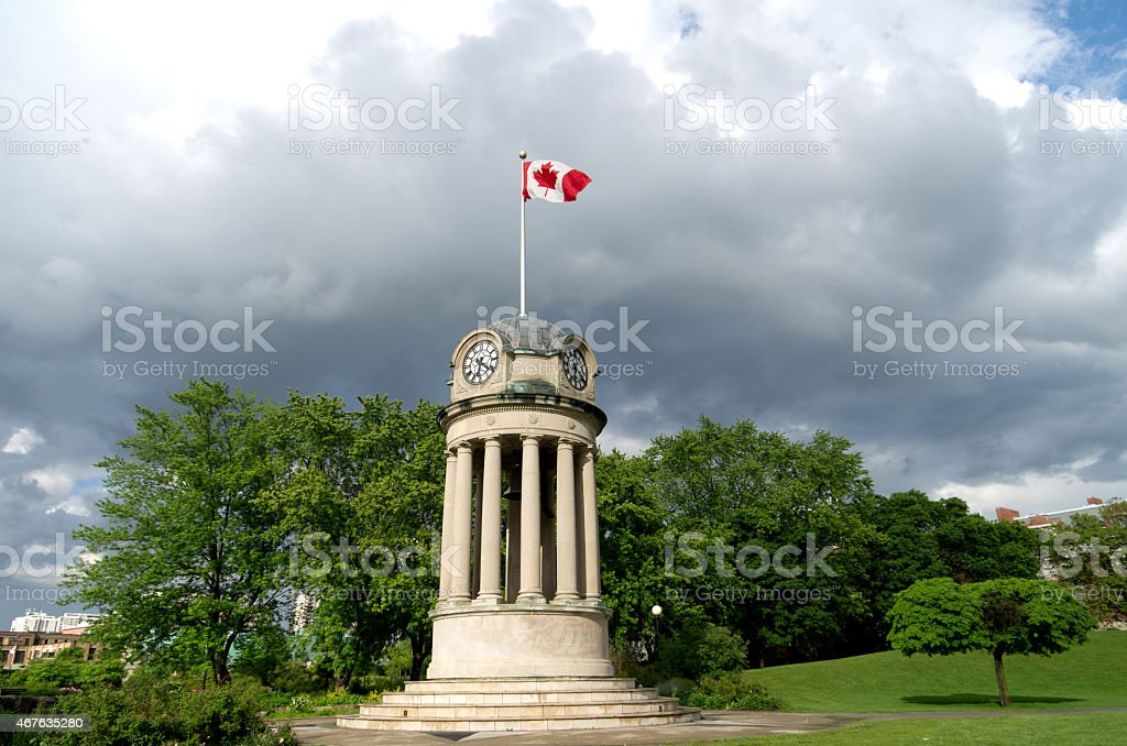 Canadian flag on clock tower with gray clouds stock photo